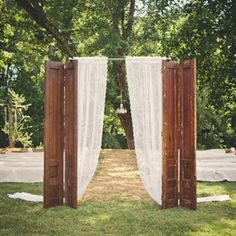 """The ceremony took place at outside, by a creek that runs through the church property.  Elisha and David placed the found antique shutters at the end of the aisle and used lace curtains for the """"grand entrance""""."""