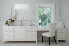 A white wingback chair sits on white marble herringbone floor tiles in front of a white drop down dressing table accented with nickel drop ring pulls and a white marble countertop and positioned beneath a window flanked by long white glass sconces mounted to a light gray upper wall.