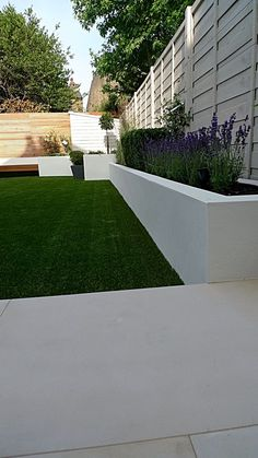 White planters with purple flowers/ lavender against grass..
