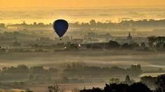 Ein Heißluft-Ballon fährt während des Sonnenaufgangs über der Stadt Godewaersvelde, Nordfrankreich.