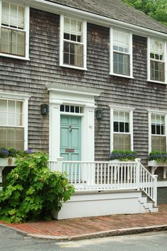 Nantucket facade is classic... shingle siding, white trim and robin's egg blue door is the icing on the cake!