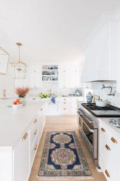 White kitchen with antique runner + brass lantern island lights | Caitlin Wilson