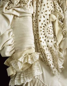c.1903-05. This refined day gown probably formed part of a springtime wardrobe. Its light colour and delicate style reflect summer fashions while the warm wool would protect against chilly weather. Woollen cloth was a fashionable material during this period, especially when combined with ornate trimmings such as hand-made lace, crocheted decoration and luxurious velvet. This example is decorated at the bodice, sleeves, and lower skirt with closely spaced cutwork edged with a fine silk cord.