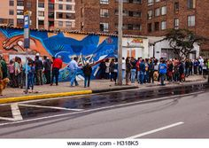 Bogota, Colombia - October 02, 2016: Voters queue up on the right, to enter a polling station on Carrera 9, in the Andean capital city of Bogota, in the South American country of Colombia, to vote on the historic Plebiscite on the peace process with FARC.To the left, behind the people is part of a mural painted in the bright colours of Latin America, dedicated to the Peace Process; the word, Paz, Spanish for peace, is partially visible.