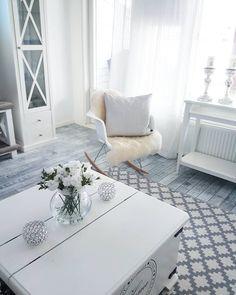 Valkoinen arkkupöytä ja Eames RAR-keinutuoli yhdistävät sisustuksen vaalean maalaisromanttisen tyylin.