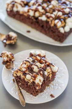 Smores Poke Cake - A supremely moist and decadent chocolate cake topped with graham crackers, marshmallows, and hot fudge!! Campfire not required for this FUN and EASY twist on smores!!