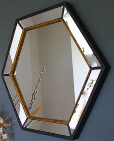 A gorgeous large hexagonal mirror in black and gold.This mirror has a lovely vintage feel , with its faceted hexagonal edges. It has a venetian style finish to the glass, with a subtle black and gold rim. It would look great above a dressing table, sink or over a fireplace. It would also make a perfect wedding present, a piece to love for a lifetime!Wood and glass.<strong>60 x 69 cm</strong>