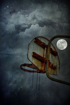 Moonlight Hoops - an almost full moon rising next to a tattered basketball hoop