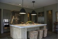 source: Dana Wolter Interiors  Kitchen design with gray walls paint color, gray kitchen cabinets, stainless steel backsplash, limed oak kitchen island with marble countertops, camel beige velvet tapered storage ottomans with nailhead trim and glossy charcoal gray island pendants.