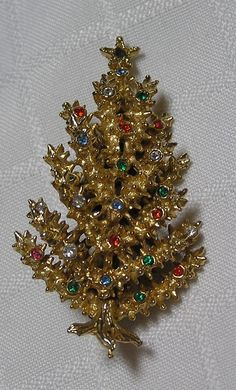 """Art Christmas rhinestone tree pin - This tree is 2.25 inches long and is crafted of a gold tone metal. The craftmanship of this pin is unique as the branches are layered and have a textured look of evergreen limbs. There are many, many multi-colored rhinestones on this beauty. Signed """"Art"""". Z"""