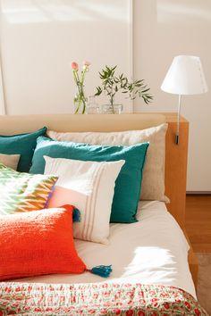 Cojines en blanco, rojo y verde sobre cama. Detrás, armario 00426441