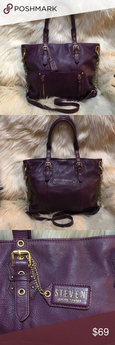 """STEVEN by Steve Madden Purple Leather Satchel NWOT STEVEN by Steve Madden 100% Purple Leather Satchel. Exterior long Strap 30% chain. Front Pocket with 2 vertical zip pockets. Rear has one small pocket. Bag Handles are adjustable Interior has 2 large compartments with a zippered center divider. One zip pocket and one slip in pocket. Magnetic snap closure. Brushed Gold Hardware. Never used. Length 14"""", Height 12"""", Handle drop 9"""", long Strap 43"""" with a 21"""" drop. NWOT Steven by Steve Madden…"""