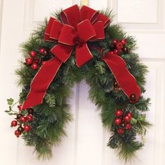 For a different look this holdiay season adorn your door with this lovely crescent shaped wreath. Lush long needle pine with cones and large red berries featuring a handtied gold egde wired holiday red velvet bow . Use as a Christmas door wreath or mai