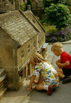 Children visit a miniature house in a model village at Bourton-on-the-Water, in Gloucestershire, England, UK (1973).