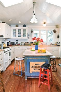 An imported antique counter from a French fish shop provides a splash of color and interest to the quiet cottage elements in the kitchen: the white planked ceiling rising to the rafters, reclaimed wooden flooring, and the cabinets' simple forms and hardware