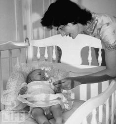 Jacqueline Kennedy offers her baby Caroline a silver rattle as she lies in her nursery crib at their Georgetown home. After a stillbirth in 1956 (they named the baby Arabella), U.S. Sen. John Kennedy and Jackie had Caroline in 1957.  Photo by Mark Shaw.
