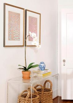 Chic foyer features a pair of seagrass baskets tucked under a clear acrylic console table, CB2 Peekaboo Console Table, topped with a white orchid placed under art.