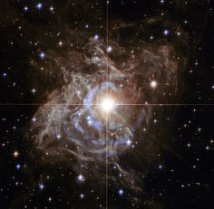 This Hubble image shows RS Puppis, a type of variable star known as a Cepheid variable. As variable stars go, Cepheids have comparatively long periods — RS Puppis, for example, varies in brightness by almost a factor of five every 40 or so days. RS Puppis is unusual; this variable star is shrouded by thick, dark clouds of dust enabling a phenomenon known as a light echo to be shown with stunning clarity.