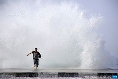 SAUDI ARABIA, Dhuba : A Saudi man runs in front of a big wave as high winds batter the coast on February 11, 2015 in the Saudi Red Sea port city of Dhuba, located in Tabuk Province, northwest of the Saudi capital Riyadh.  AFP PHOTO / MOHAMMED ALBUHAIS