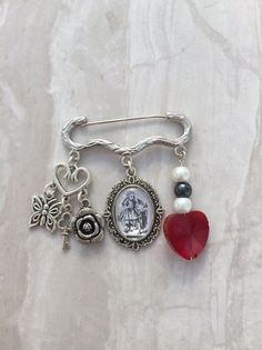 Beautiful Alice in Wonderland inspired cameo and charm brooch.  Silver kilt pin measuring 45mm in length with an antique style original image Alice in Wonderland cameo, silver heart hanger with silver butterfly, key and rose charm and a crystal heart heart with glass faux pearl beads.  Ideal gift for any Alice fan, birthday gift, Christmas present Comes in an organza gift bag.