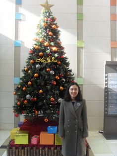 After the church service in front of a Christmas tree in the building. Gave food to Susan and arrived at the home with Sujung.