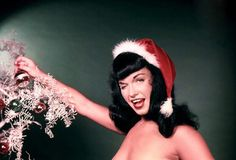 With her coy smile hiding as many secrets as the Mona Lisa and her iconic bangs which are still emulated by wanna-be pin-up queens the world over, Bettie Page was and is America's Sweetheart.   Here's a Christmas treat, just like Grandpa used to peep out in the shed on a cold Winter's day: a gallery of lowbrow art photographs from the mid-20th Century depicting Bettie, celebrating the most wonderful time of the year.  God bless us, each and every one.