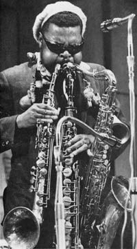 Rashaan Roland Kirk-blind (and was still active even after a stroke) visionary. Used much innovation and gimmickry in his music. Yes, he could play 3 saxs at once, and he also used circular breathing techniques to get sustains. He promptly died off stage right after bowing at the end of a performance in Bloomington, IN.