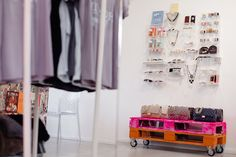 Amazing closet features wall mounted acrylic organizers filled with jewelry, perfumes and sunglasses over a pink and orange plank bench on wheels lined with Chanel 2.55 bags in various colors.