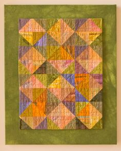 """How to mount an art quilt on canvas, with a fabric border:  """"I picked up four  canvas frames at Michael's the other day for a ridiculously low price... Today, I put a facing on my small, green half-square triangle quilt and then mounted it on the canvas frame.""""  Posted by Fibercrush"""