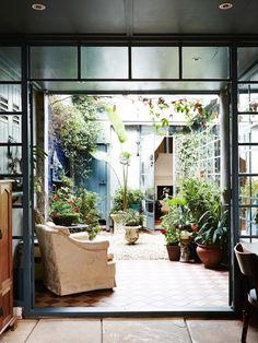 【リビング・ダイニングの隣の中庭リゾート】一人掛けソファの置かれたテラスの屋外リビング | 住宅デザイン もっと見る