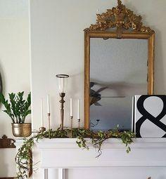 Antique gold mirror, Vintage brass candlesticks, white fireplace. Simple mix of vintage and modern decor. Instagram @beesnburlap Home decor blog beesnburlap.com