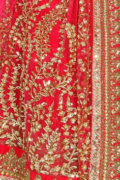 This Sabyasachi lehenga is featuring in a pink net flared jacket heavily embroidered with sequins, gota, dabka and zari in floral design. This Pink Sabyasachi lehenga has potli buttons on yoke and sli