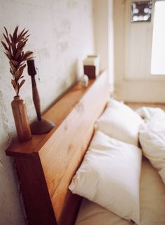 Add a mini-shelf and some thickness to the headboard; will also hide the structural pieces without adding more distance between the bed and the wall