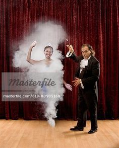 Magician making woman appear out of thin air - Stock Photo