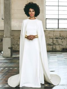 Solange Knowles wears a white wedding gown with an attached cape and gold jewelry
