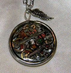 "This crazy piece is Stem punk inspired and is a small piece for those who don't like large jewelry. Antiqued silver plated Wing charm adorns this ice resin pendant with watch parts, a lizard charm inlaid and a tiny green Swavorski crystal for glitter. 20"" silver tone chain. Simple and elegant steam-punk for the office"