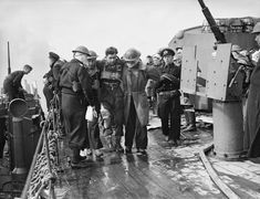 D-Day ~ Operation Overlord (The Normandy Landings): D-Day 6 June 1944, Beach casualties being helped to the sick-bay on board HMS FROBISHER. The cruiser had helped bombard the enemy coastal positions during the week before D-Day.