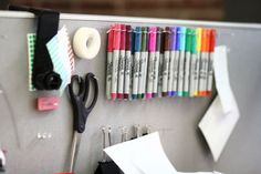 Everyday office supplies on a cubicle wall