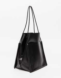 Soft, unlined leather everyday tote bag from Building Block. Features modern, low-key styling with a rubber spaghetti shoulder strap, and two exterior pouch pockets.   	•	Fold over leather hand bag  	•	Rubber spaghetti strap  	•	100% Leather