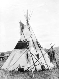 """A tipi in Siksika camp. Montana. Medicine """"bundles""""  on tripod. Early 1900s. Photo by Walter McClintock."""