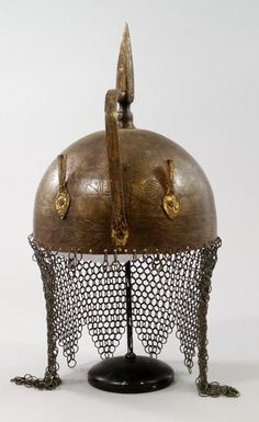 An Indo Persian steel khula khud with chiselled figural decoration, spike finial and chain mail - Price Estimate: £200 - £300