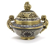 A cloisonné enamel incense burner  Qianlong Period (1736 - 1795)  of bombé form, cast with two intricate chilong handles, the body finely enamelled with four lotus blooms against a white-enamelled ground, framed above by a border of lotus lappets, the domed cover similarly enamelled with a continuous lotus scroll and lappet border, with gilt bronze open work lotus band, and surmounted by an openwork chilong finial, 18cm wide