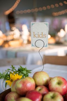 Kids table with bowl of apples centerpiece. #kidstable #apples #farmwedding