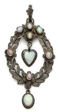 A silver and opal pendant, attributed to Arthur and Georgie Gaskin, circa 1905. The foliate pendant set with oval cabochon opals and suspending a similar and heart-shaped opal, to a later fancy-link necklace, maker's mark, lengths: pendant 5.6cm, chain 41.0cm, fitted case by the Tadema Gallery.