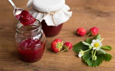 Homemade strawberry jam (marmelade) in jars on wooden background. - stock photo