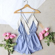 Gorgeous chambray details adorn this sweet lace trimmed romper. Detailed with a soft white lace, this romper has a v-neck bust, gathered waist, and strappy cross back closure. Adjustable with a fully