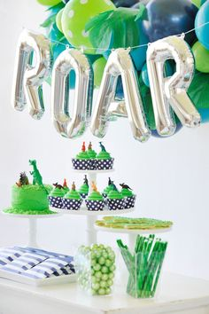 "Watch out! This dinosaur themed dessert table has us screaming! Jungle themed balloons. Silver letter ""roar"" balloons. T-Rex/Dinosaur Party styling by Happy Wish Company. Photography by Tammy Hughes Photography. Stationery by Minted artist, Patricia Wallace."