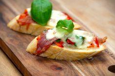 Bruschetta med mozzarella er en skøn forret fra Italien, der dog sagtens også kan nydes uden ost. Smør brødet med hvidløgsolie, og læg så de øvrige ingredienser oven på, inden bruschettaen bages i ovnen. Foto: Guffeliguf.dk.