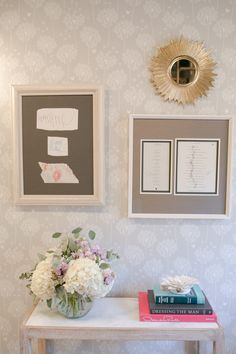 dandelion wallpaper hung with personal art and a gold starburst mirror and hydrangea floral arrangement on a white console table