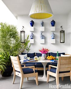 The outdoor dining area of designer Robert Passal's Miami Beach apartment is sheltered from the sun and furnished with comfortable chairs and a sofa.